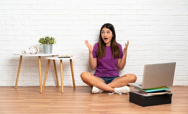 놀라운 표정으로 실내에서 바닥에 앉아 노트북을 가진 젊은 여자
