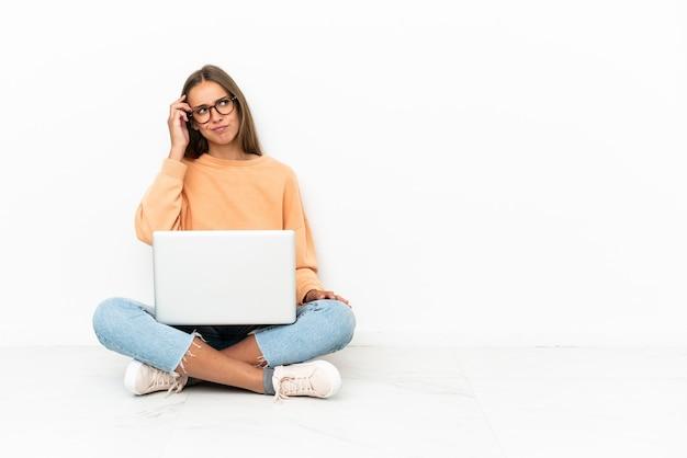 의심을 갖는 바닥에 앉아 혼란스러운 얼굴 표정으로 노트북을 가진 젊은 여자