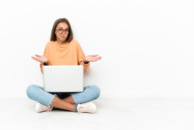손을 올리는 동안 의심을 갖는 바닥에 앉아 노트북을 가진 젊은 여자