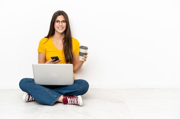 Молодая женщина с ноутбуком сидит на полу, держа кофе на вынос и мобильный