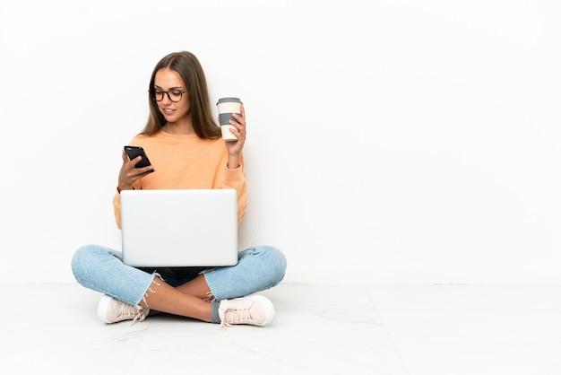 持ち帰り用のコーヒーと携帯電話を持って床に座っているラップトップを持つ若い女性