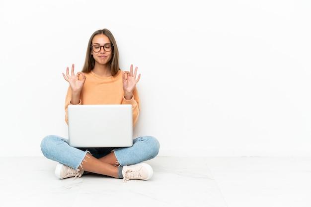 젠 포즈에서 바닥에 앉아 노트북을 가진 젊은 여자
