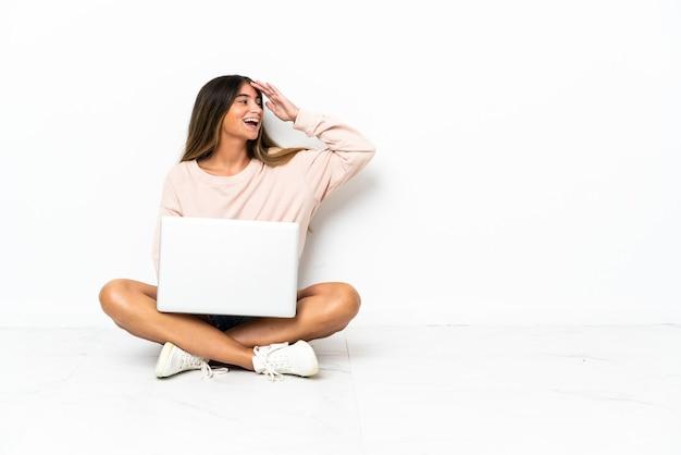 白い背景に隔離された床にノートパソコンを持った若い女性が何かに気づき、解決策を考えている