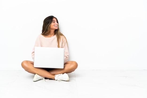 측면 위치에서 흰색 배경에 고립 된 바닥에 앉아 노트북을 가진 젊은 여자