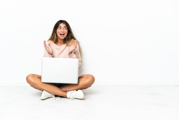 驚きの表情で白い背景で隔離の床に座っているラップトップを持つ若い女性