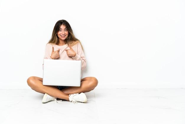 놀라운 표정으로 흰색 배경에 고립 된 바닥에 앉아 노트북으로 젊은 여자