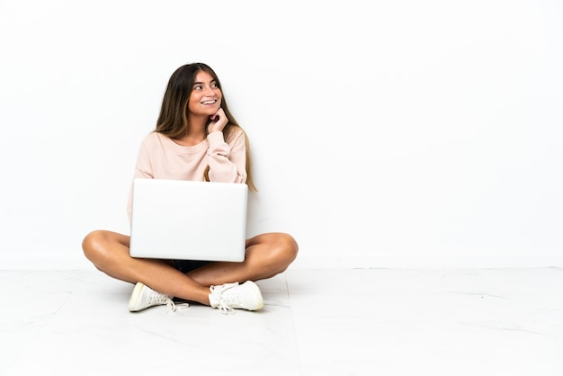 Молодая женщина с ноутбуком, сидя на полу, изолированном на белом, думая об идее