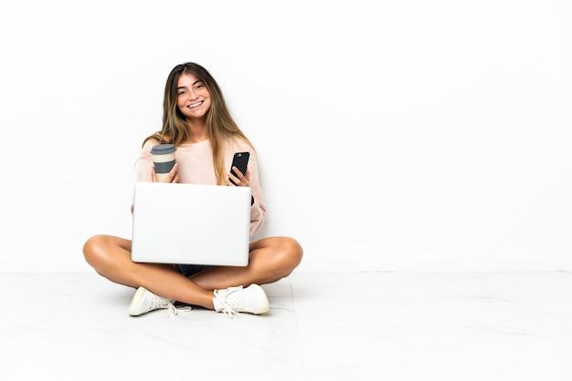 Молодая женщина с ноутбуком сидит на полу, изолированном на белой стене, держит кофе на вынос и мобильный