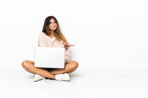 노트북을 향해 웃고 보면서 아이디어를 제시하는 흰 벽에 고립 된 바닥에 앉아있는 젊은 여자