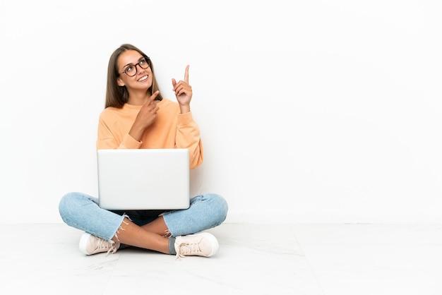 검지 손가락으로 좋은 아이디어를 가리키는 바닥에 앉아 노트북을 가진 젊은 여자