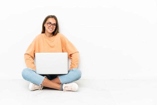 床に座って腰に腕を組んでポーズをとって笑顔のラップトップを持つ若い女性