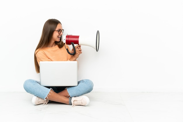 Молодая женщина с ноутбуком сидит на полу и кричит в мегафон