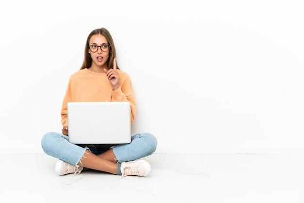 손가락을 가리키는 아이디어를 생각하는 바닥에 앉아 노트북을 가진 젊은 여자