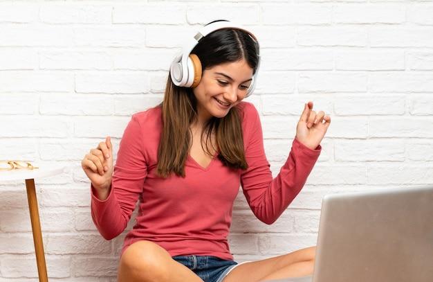 Молодая женщина с ноутбуком, сидя на полу
