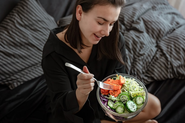 ベッドに野菜と新鮮なサラダの大きなボウルを持つ若い女性