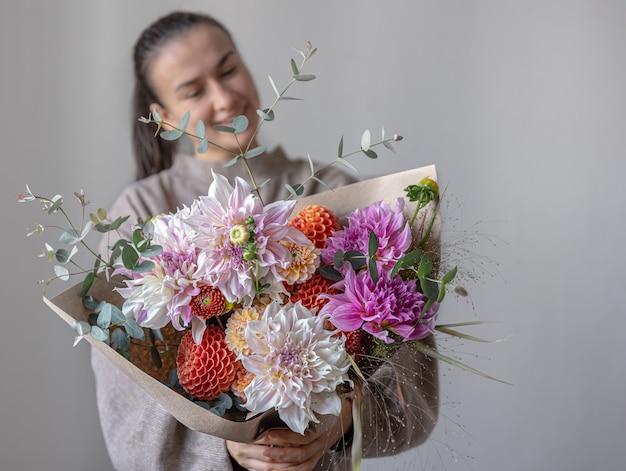 菊の大きなお祭りの花束を持つ若い女性