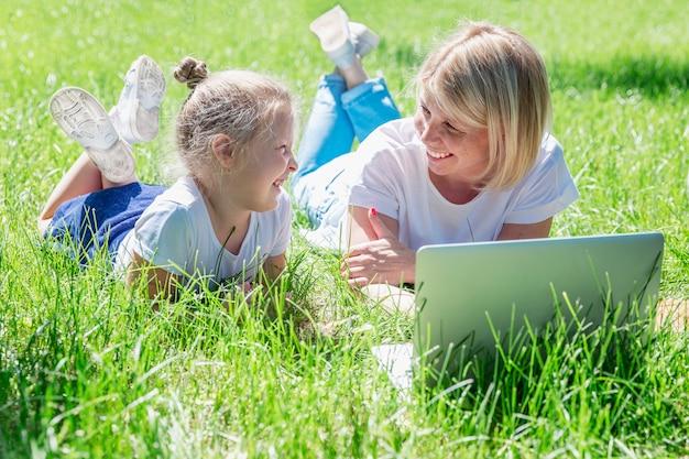 小さな娘を持つ若い女性は、ラップトップで公園に横たわり、笑います。ブログ、オンライントレーニング、通信教育。