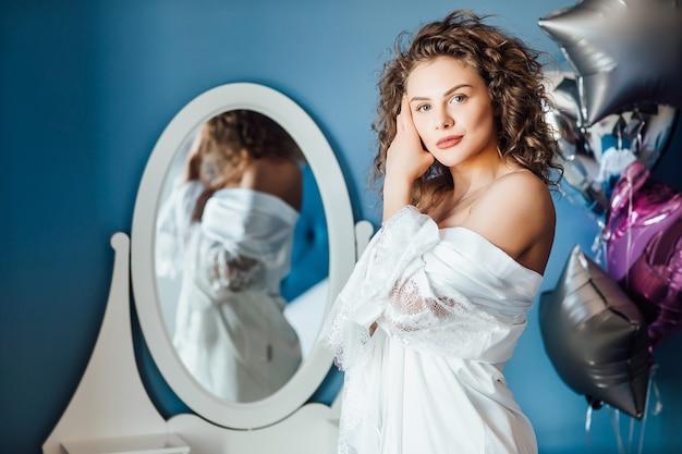 長い巻き毛のポーズの若い女性