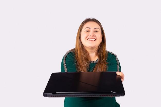 긴 머리와 노트북 컴퓨터를 가진 젊은 여성이 녹색 드레스를 입고 회색 배경에 웃고 있다