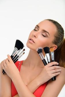 Молодая женщина с большим количеством кистей для макияжа.