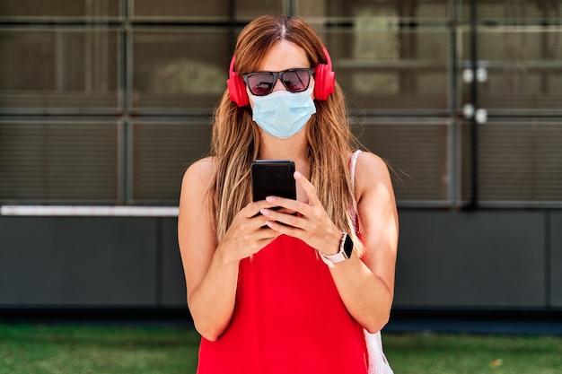 市内で彼女の携帯電話を使用してマスクを持つ若い女性。