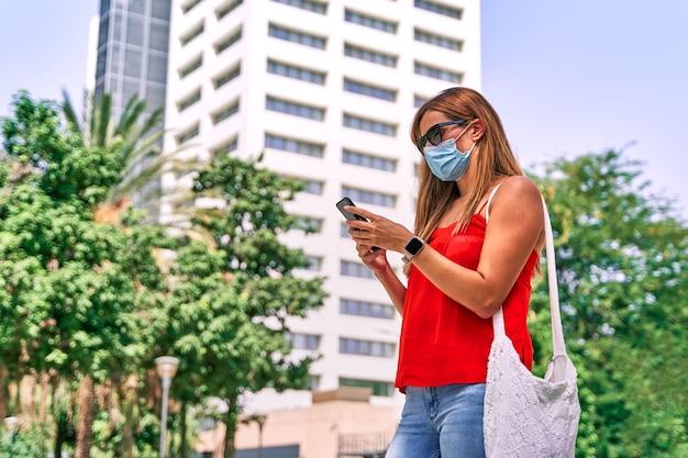彼女の携帯電話を使用してマスクを持つ若い女性。