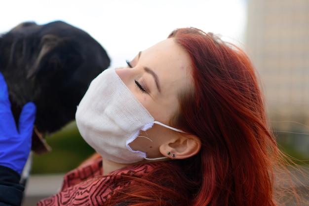 Молодая женщина с медицинской маской и ее собакой