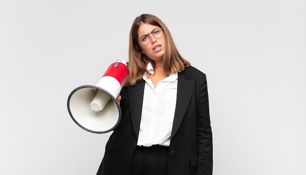 Молодая женщина с мегафоном в недоумении и недоумении, с тупым, ошеломленным выражением лица смотрит на что-то неожиданное
