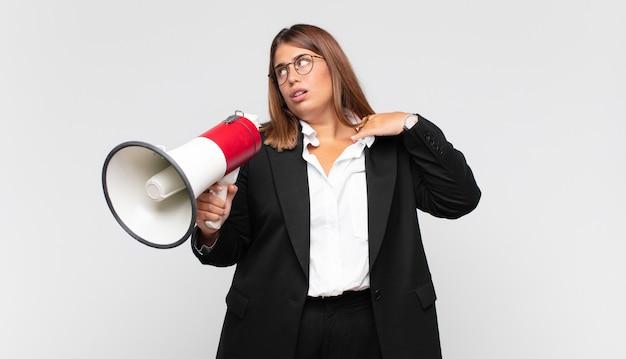 メガホンの若い女性は、ストレス、不安、疲れ、欲求不満を感じ、シャツの首を引っ張って、問題で欲求不満に見えます