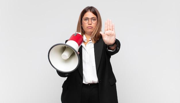 Молодая женщина с мегафоном выглядит серьезной, суровой, недовольной и сердитой, показывая открытую ладонь, делая жест стоп
