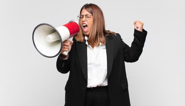 확성기가 화난 표정으로 공격적으로 외치거나 주먹으로 성공을 축하하는 젊은 여성