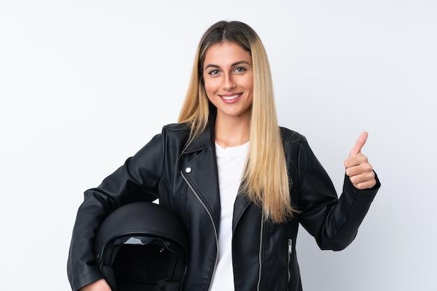 親指ジェスチャーを与える分離の白い壁の上のオートバイのヘルメットを持つ若い女性