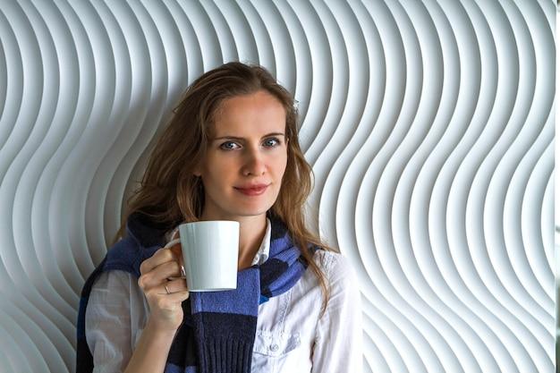 壁のそばに立ってカメラを見ている彼女の手にマグカップを持つ若い女性