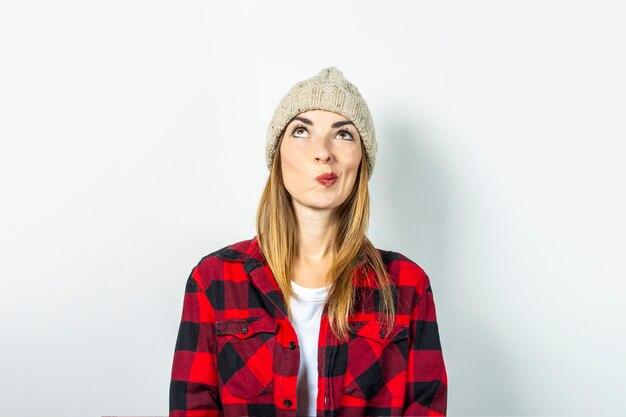 잠겨있는 얼굴을 가진 젊은 여자는 모자, 빨간 셔츠와 흰색 표면에 흰색 티셔츠에 뭔가 꿈