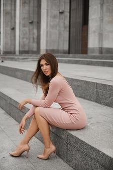 完璧なボディとベージュのタイトなドレスと都会の背景でポーズをとる流行の靴の長いセクシーな脚を持つ若い女性