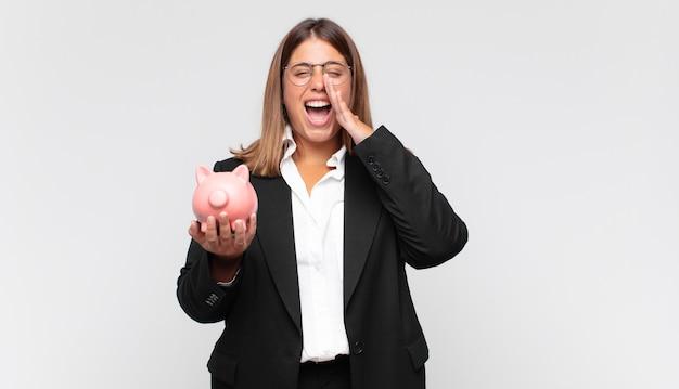 貯金箱を持った若い女性は、幸せで、興奮して、前向きに感じ、口の横に手を置いて大きな叫び声を上げ、声をかけます
