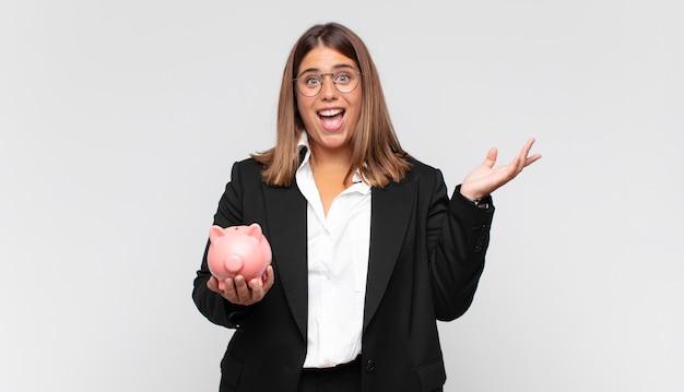 幸せ、驚き、陽気に感じ、前向きな姿勢で笑顔で、解決策やアイデアを実現する貯金箱を持つ若い女性