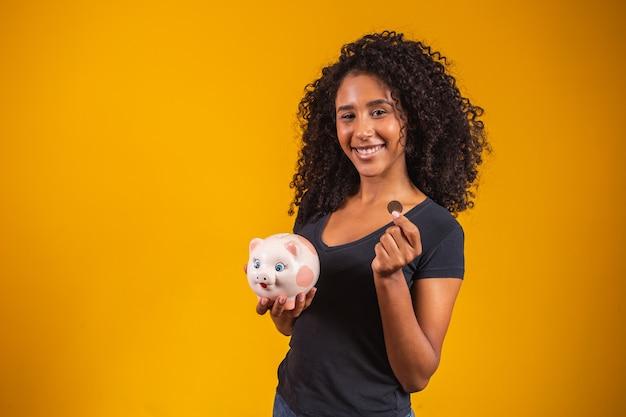 固体の背景に貯金箱を持つ若い女性