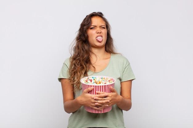 ポップコンのバケツを持った若い女性は、嫌悪感とイライラを感じ、舌を突き出し、厄介で厄介なものを嫌います