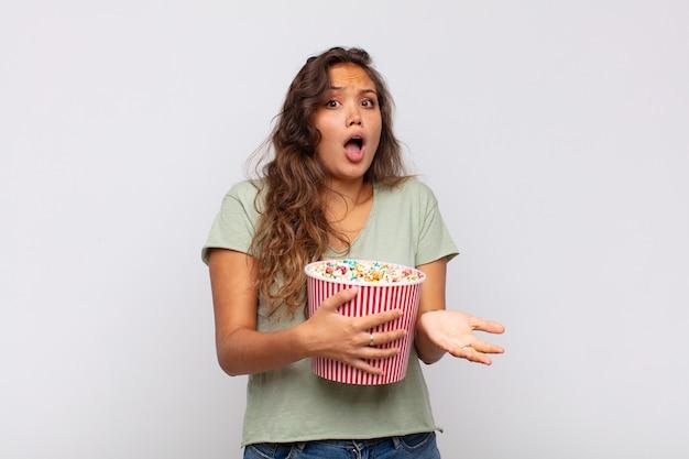 팝콘 양동이를 든 젊은 여성이 극도로 충격을 받고 놀라고 불안하고 당황하며 스트레스를 받고 겁에 질린 표정으로