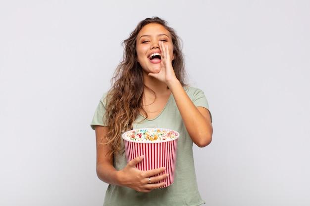 Молодая женщина с ведром поп конрс чувствует себя счастливой, взволнованной и позитивной, громко кричит, прижав руки ко рту, выкрикивая