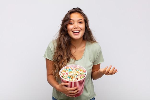Молодая женщина с ведром поп conrs чувствует себя счастливой, удивленной и веселой, улыбается с позитивным настроем, реализует решение или идею