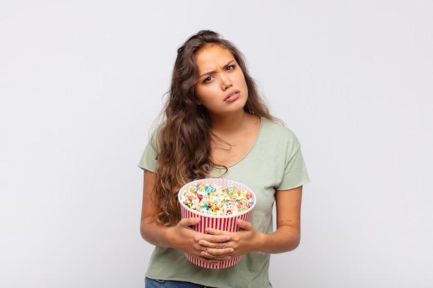 ポップなconrsバケツを持った若い女性は、戸惑い、混乱し、予想外の何かを見ている愚かな、唖然とした表情で