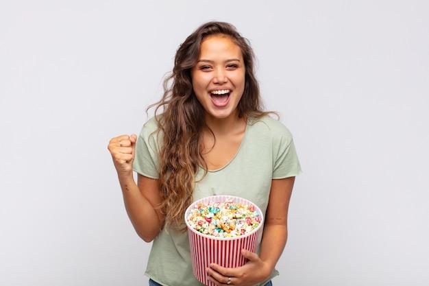 팝콘 양동이를 든 젊은 여성이 충격을 받고, 흥분하고, 행복하고, 웃고, 성공을 축하하며, 와우라고 말합니다!