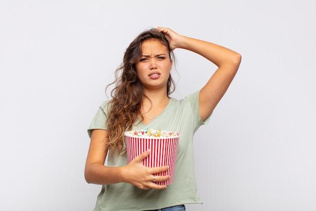 Молодая женщина с ведром для поп-конра чувствует стресс, беспокойство, беспокойство или испуг, с руками за голову, паникует из-за ошибки