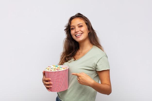 팝 conrs 버킷을 가진 젊은 여자가 흥분하고 놀란 찾고 측면을 가리키는 위쪽으로 공간을 복사