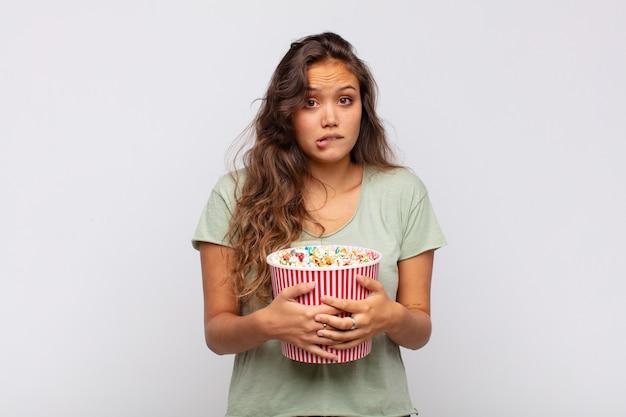 Молодая женщина с ведром для поп-конра выглядела озадаченной и смущенной, нервно закусив губу, не зная ответа