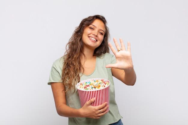 Молодая женщина с ведром для поп-конра улыбается и выглядит дружелюбно, показывает номер пять или пятое с рукой вперед, отсчитывая