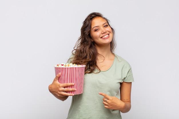 팝콘 양동이를 가진 젊은 여성은 즐겁게 웃고 행복하며 옆과 위쪽을 가리키며 복사 공간에 물건을 보여줍니다.