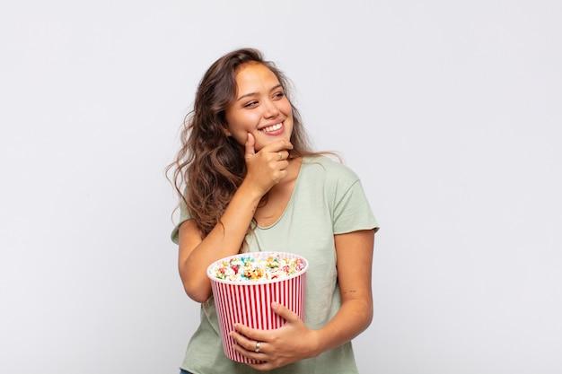Молодая женщина с ведром для поп-конра улыбается со счастливым, уверенным выражением лица, положив руку на подбородок, задается вопросом и смотрит в сторону